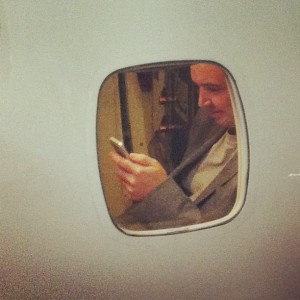 Business travelers will be able to use their wifi enabled cell phones more in 2017. This is a man texting on a plane.