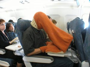 A man sitting on an airplane wearing a knit tube over his head and his laptop computer. His hands fit into little openings near the laptop.