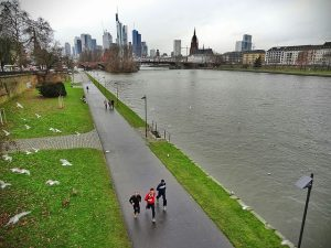 People jogging in Frankfurt am Mein. Could be on a business trip, or they could just live there. We don't know.