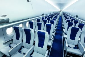 The seat you choose for your air travel says a lot about you. This is a picture of an empty SuperJet plane with blue seats and blue carpets.