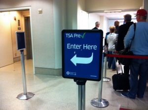 TSA PreCheck sign showing the way to an empty pathway, next to a line packed with people.