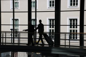 Your business travel doesn't have to be stressful. Silhouette of a man walking through an airport.