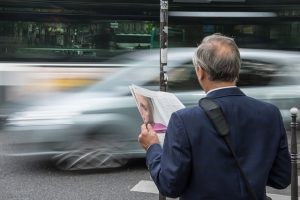 An older man holding a newspaper waiting for a car to pass. Different generations approach their business travel differently.