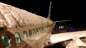 This is a common sight during travel in winter. This is a Norwegian SAS airplane on the ground and covered with snow.
