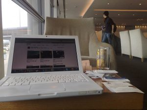 Business travel often means working in an airport between flights. This is a photo of a white MacBook Pro taken in the Hong Kong airport.