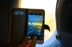 A photo of a smartphone taking a photo of a plane wing. More people are using smartphones to book their travel.