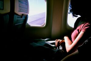 A woman business traveler sitting on an airplane. Business travel can help entrepreneurs improve the way they work and function.