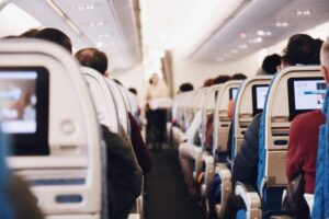 Inside an airplane looking down the main aisle. There are several rudeness prevention secrets you should know before you travel.