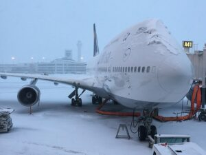A Lufthansa airplane covered in snow. This is a common sight if you take a lot of winter business travel trips.