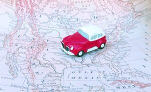 Photo of a toy car on a map. A road trip is a great way to experience domestic travel.