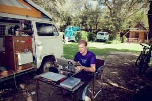 A man sitting at his computer outside, next to his van, living the life of a digital nomad.