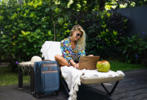 A woman sitting on a lounge chair with her laptop, next to her Travelpro bag. She's a digital nomad, able to work from wherever she can find wifi.