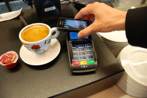 Someone paying with their phone, one form of contactless payment