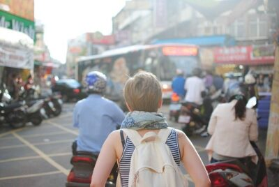 Young woman walking in a busy city. Consumer confidence in travel is growing.