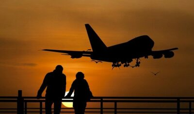Photo of a travel couple watching the sunset as a plane flies overhead.