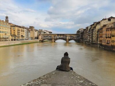Woman sitting on a bank looking out over a river in Italy. This is something you can do on a solo travel trip.