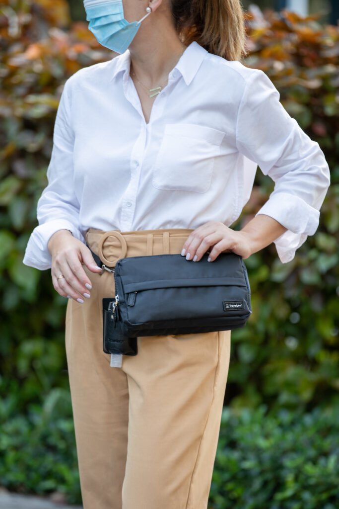 A woman wearing comfortable travel apparel and carrying a Travelpro Convenience Pack.