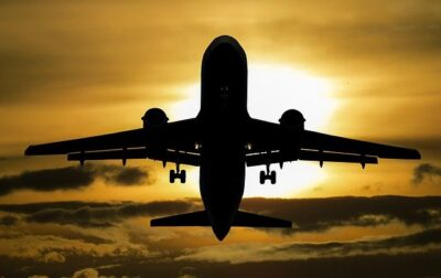 Silhouette of an airplane against the sun. If you're going to be booking a trip this year, make sure you follow these steps.