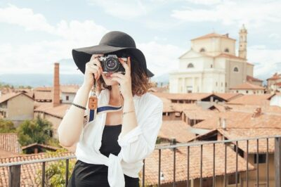 A woman taking a photo in front of a tourist destination. She looks like she could be a frequent traveler. You could be too.