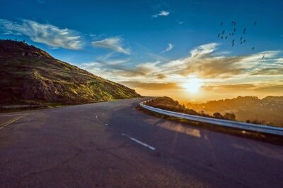 A winding road driving into the sunset. This is a great look for an extended road trip.