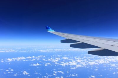 Looking out over an airplane wing with a deep blue sky in the background and over a few sparse clouds. A beautiful photo of air travel.