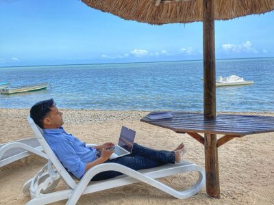 Photo of a man working at the beach on his laptop. A typical digital nomad in their summer surroundings.