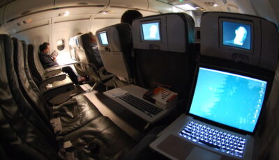 The business travel holy grail! A whole airplane row to yourself. Tray is down, and there's a laptop on it.